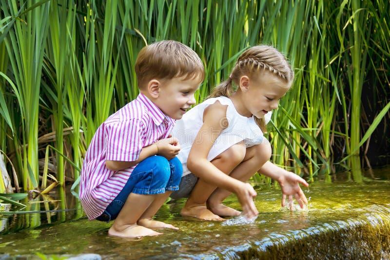 Ragazzo e ragazza che si siedono in acqua vicino alla piccola cascata fotografia stock