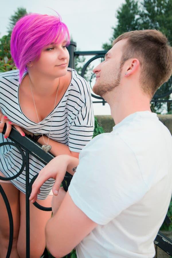 Ragazzo e ragazza che stanno vicino ad un'inferriata fotografia stock