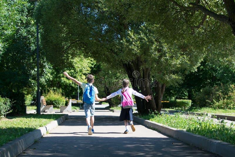 Ragazzo e ragazza dopo scuola con le borse piene dei manuali che ritornano a casa con tenersi per mano del parco immagini stock libere da diritti
