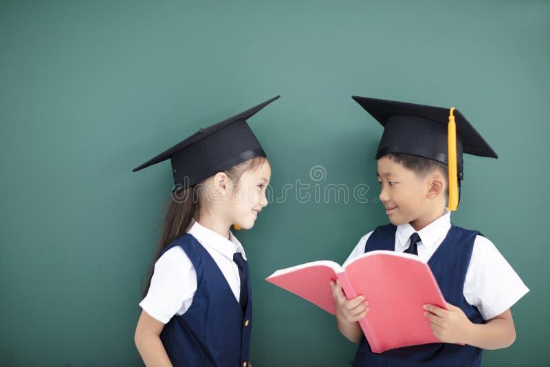 ragazzo e ragazza nel cappuccio e nello studio di graduazione immagine stock libera da diritti