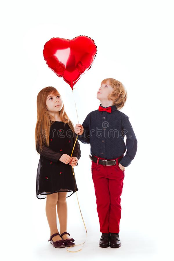Ragazzo e ragazza su un fondo bianco che tiene un cuore di rosso del pallone immagine stock libera da diritti