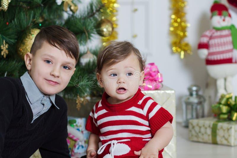 Ragazzo e ragazza vicino ad un albero di Natale immagini stock libere da diritti
