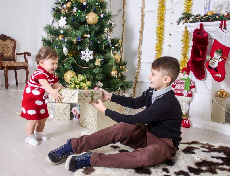Ragazzo e ragazza vicino ad un albero di Natale fotografia stock libera da diritti