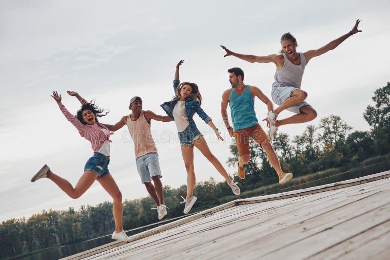 Ragazzo e ragazze che si siedono sullo scrittorio praticante il surfing e sullo sguardo sul mare blu fotografie stock
