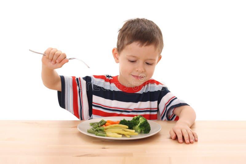 Ragazzo e verdure cucinate fotografia stock