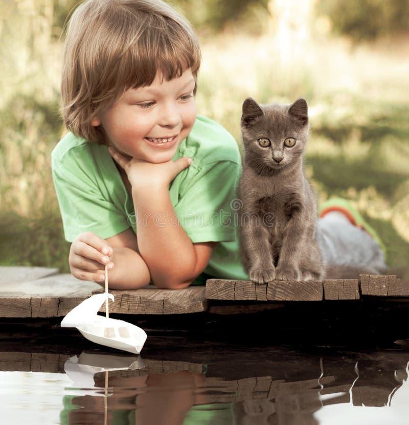 Ragazzo ed il suo gattino caro che giocano con una barca dal pilastro nella sera di estate dello stagno immagini stock libere da diritti