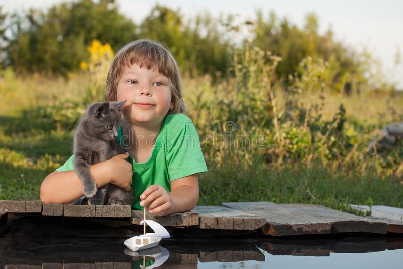 Ragazzo ed il suo gattino caro che giocano con una barca dal pilastro in stagno fotografia stock libera da diritti