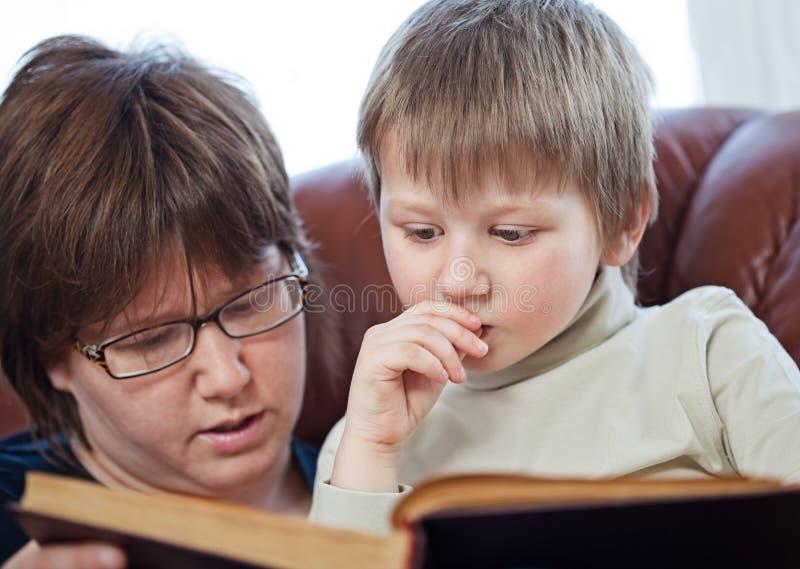 Ragazzo ed il suo libro di lettura della mamma insieme fotografie stock