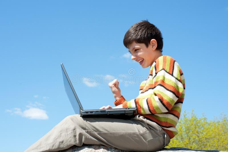 Ragazzo emozionante che gioca con il computer portatile senza fili immagini stock