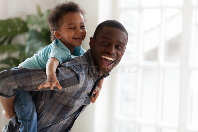 Ragazzo emozionante del bambino che gioca con il padre africano felice a casa fotografie stock