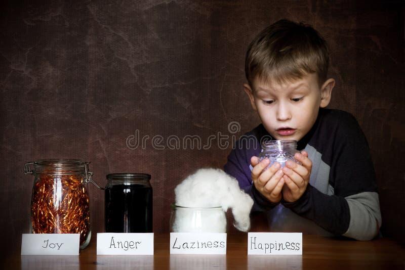 Ragazzo europeo di aspetto In barattoli accanto lui gioia, rabbia, pigrizia Nelle mani di un bambino un barattolo di felicit immagine stock libera da diritti