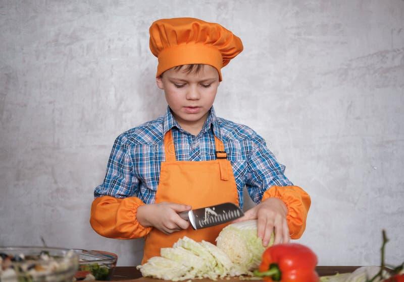 Ragazzo europeo nel costume del cavolo cinese del coltello di taglio del cuoco unico per insalata immagini stock libere da diritti