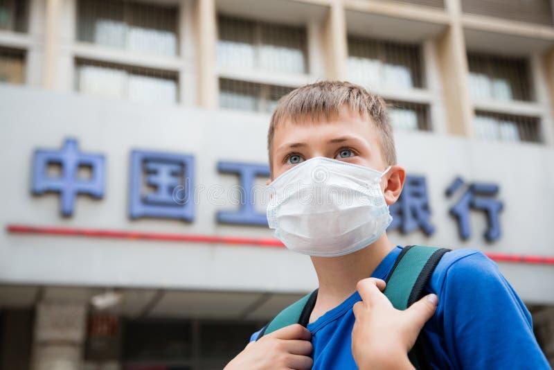 Ragazzo europeo in una maschera protettiva su una via a Pechino immagine stock libera da diritti