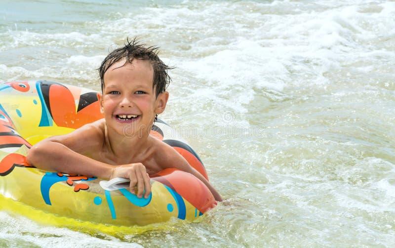 Ragazzo felice bello con l'anello gonfiabile che galleggia sul mare, sulle onde e sulla tempesta, fotografia stock libera da diritti