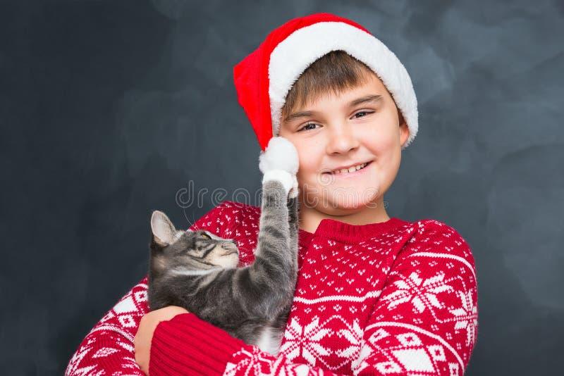 Ragazzo felice in cappuccio rosso del ` s del nuovo anno con il gattino grigio in sue mani sopra immagine stock libera da diritti