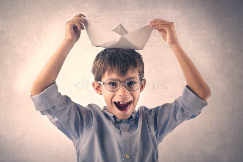 Ragazzo felice che gioca con una barca di carta immagine stock libera da diritti