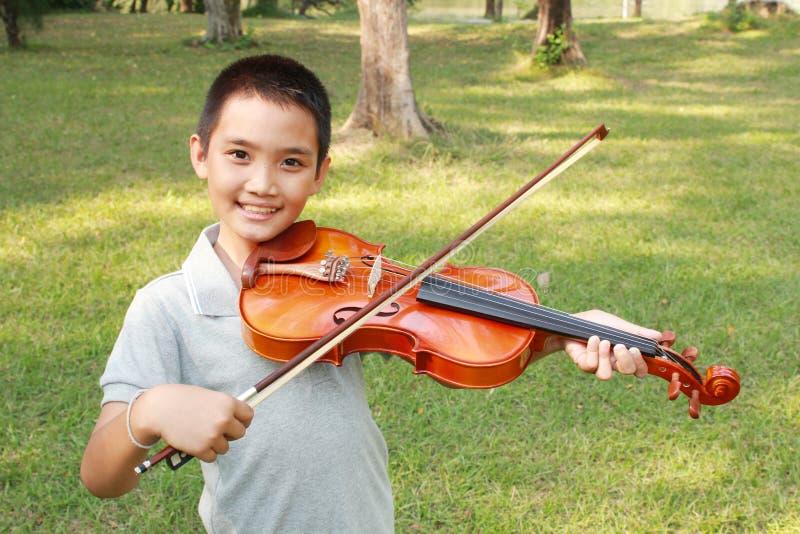 Ragazzo felice che gioca il suo violino fotografia stock libera da diritti