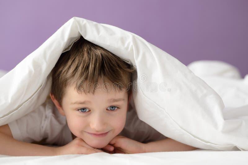 Ragazzo felice che gioca a letto sotto una coperta o un copriletto bianca immagine stock libera da diritti