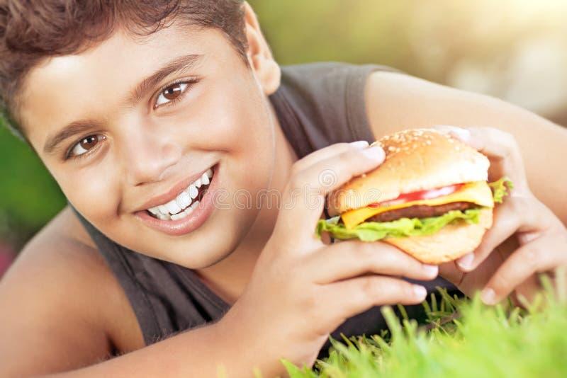 Ragazzo felice che mangia hamburger fotografia stock libera da diritti