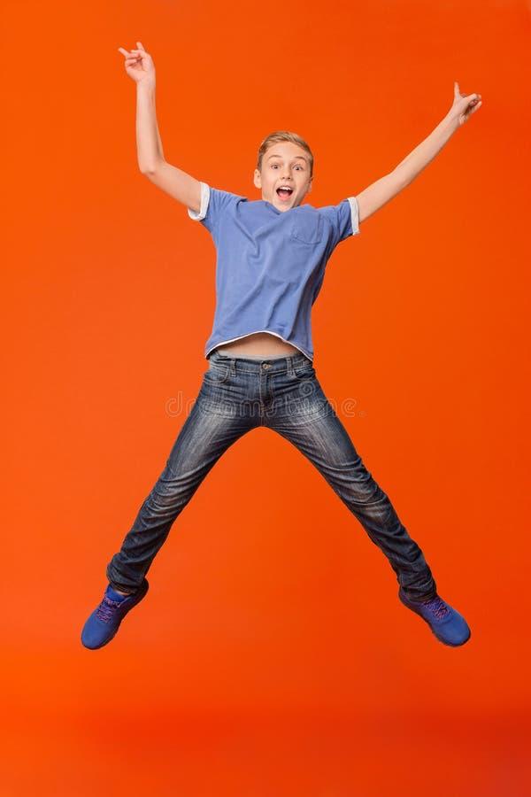 Ragazzo felice che salta e che solleva le sue mani su fotografie stock libere da diritti