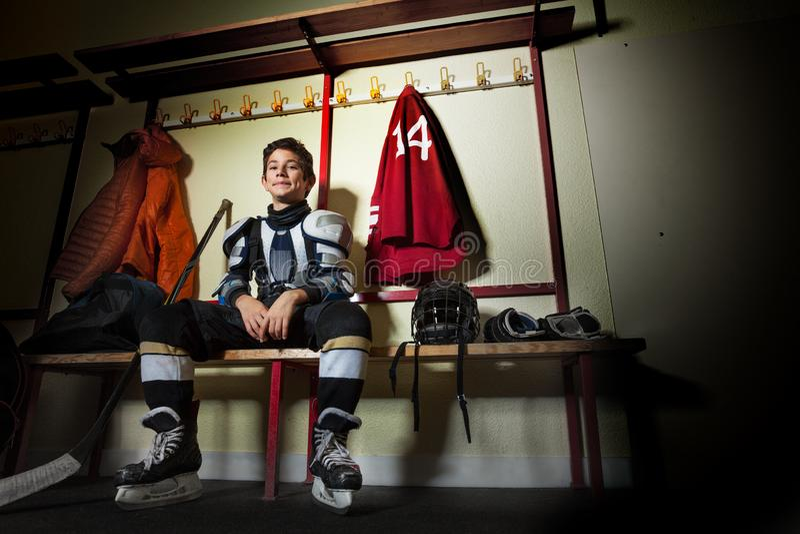Ragazzo felice che si siede nello spogliatoio del hockey su ghiaccio fotografia stock libera da diritti