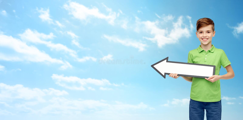 Ragazzo felice che tiene l'insegna in bianco bianca della freccia immagine stock