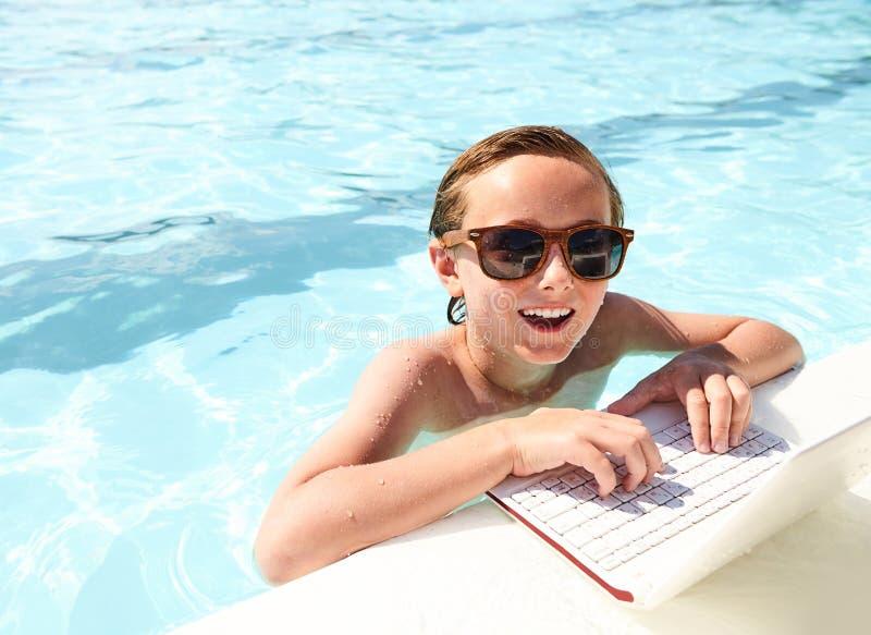 Ragazzo felice che utilizza computer portatile nello stagno alla stazione turistica estiva fotografie stock libere da diritti