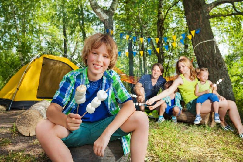 Ragazzo felice con la caramella gommosa e molle arrostita al campeggio immagini stock libere da diritti