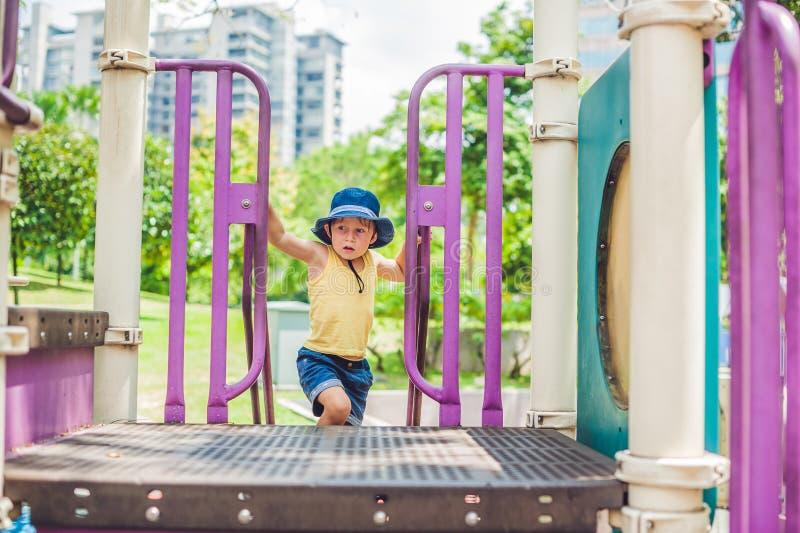 Ragazzo felice del bambino che gioca al campo da giuoco variopinto Bambino adorabile divertendosi all'aperto immagine stock libera da diritti