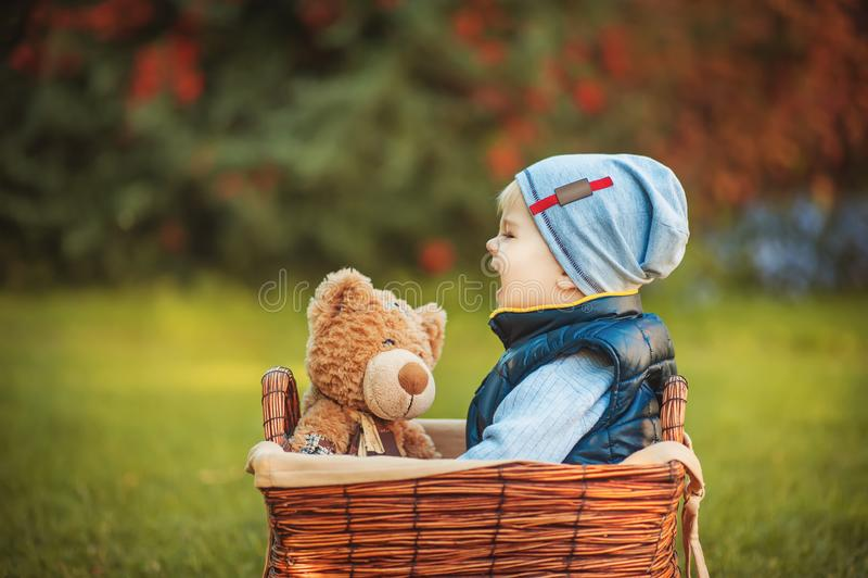 Ragazzo felice del bambino che gioca con il giocattolo dell'orso e che grida mentre sedendosi merce nel carrello sul prato ingles fotografia stock libera da diritti