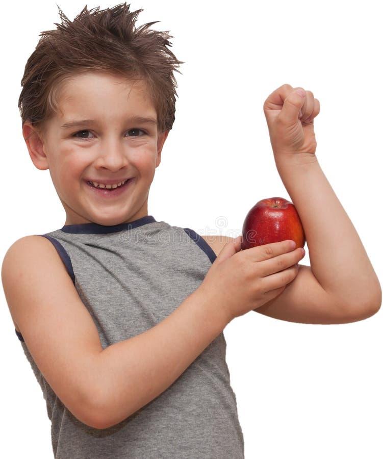 Ragazzo felice del bambino che mostra la mela del muscolo fotografie stock libere da diritti