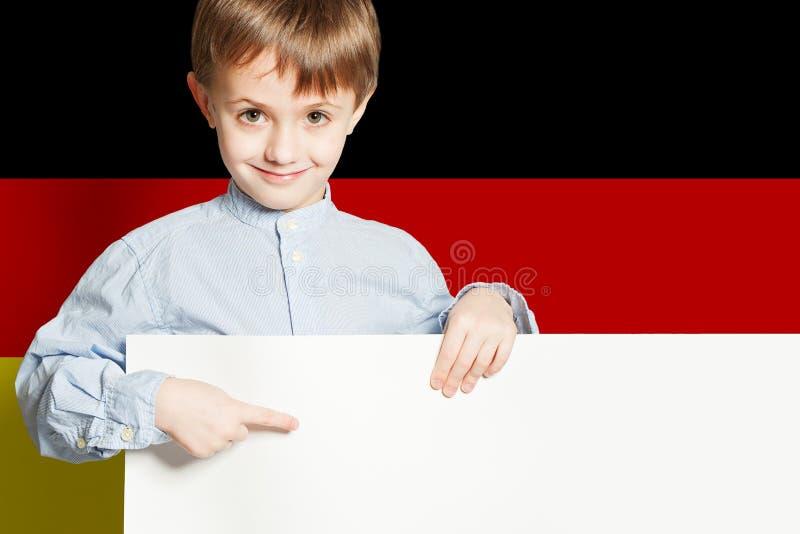 Ragazzo felice del bambino che tiene insegna vuota bianca sui precedenti della bandiera di Deutsch immagine stock