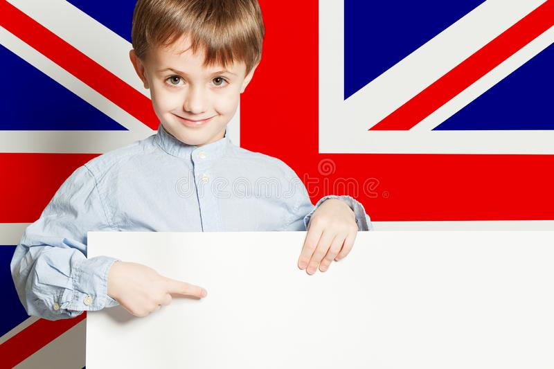 Ragazzo felice del bambino che tiene l'insegna vuota bianca del cartone contro i precedenti BRITANNICI della bandiera fotografia stock libera da diritti