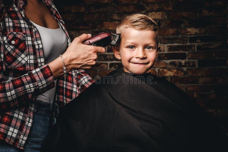 Ragazzo felice del bambino in età prescolare che ottiene taglio di capelli Il parrucchiere dei bambini con il regolatore sta tagl fotografia stock libera da diritti