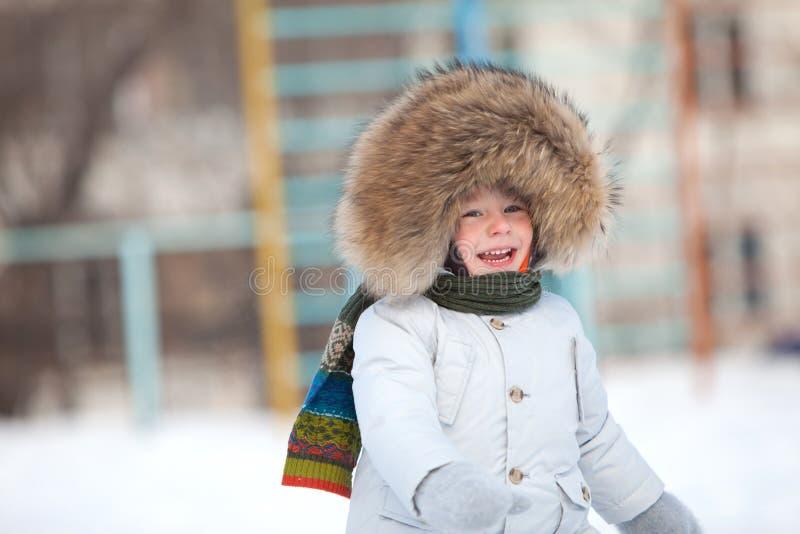 Ragazzo felice del bambino in rivestimento di inverno con il testo fisso della pelliccia fotografia stock libera da diritti