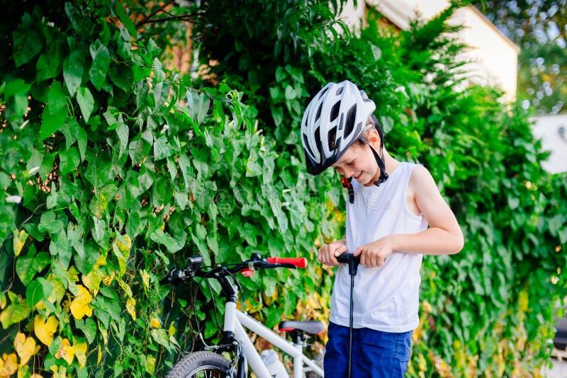 Ragazzo felice del piccolo bambino in casco bianco che gonfia gomma in sua bicicletta immagini stock libere da diritti