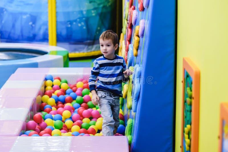Ragazzo felice divertendosi nel pozzo della palla nel parco di divertimenti dei bambini e nel centro dell'interno del gioco Bambi immagini stock libere da diritti