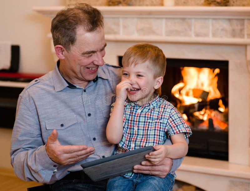 Ragazzo felice ed suo nonno che per mezzo di un computer della compressa fotografia stock libera da diritti