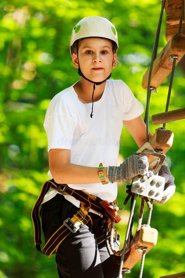 Ragazzo felice, sveglio, giovane in maglietta bianca e casco divertendosi e giocando al parco di avventura, fotografia stock
