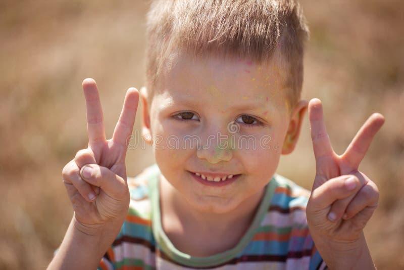 Ragazzo fresco in pieno di polvere colorata da ogni parte del fronte immagini stock libere da diritti
