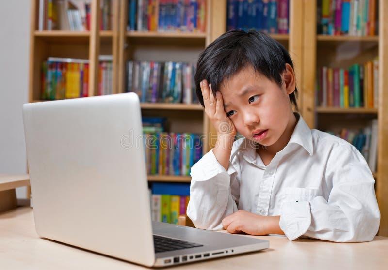 Ragazzo frustrato in camicia bianca davanti al computer portatile fotografia stock libera da diritti