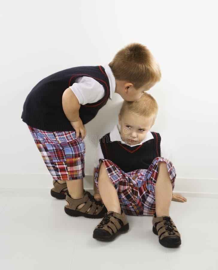 Ragazzo gemellare che bacia il suo fratello. fotografia stock libera da diritti