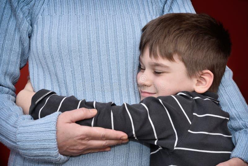 ragazzo i suoi giovani abbraccianti della madre immagine stock
