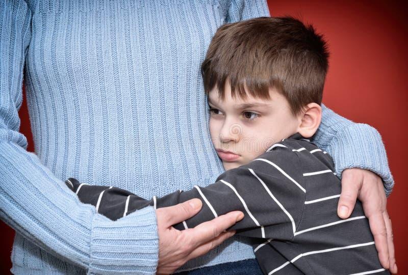 ragazzo i suoi giovani abbraccianti della madre fotografie stock libere da diritti