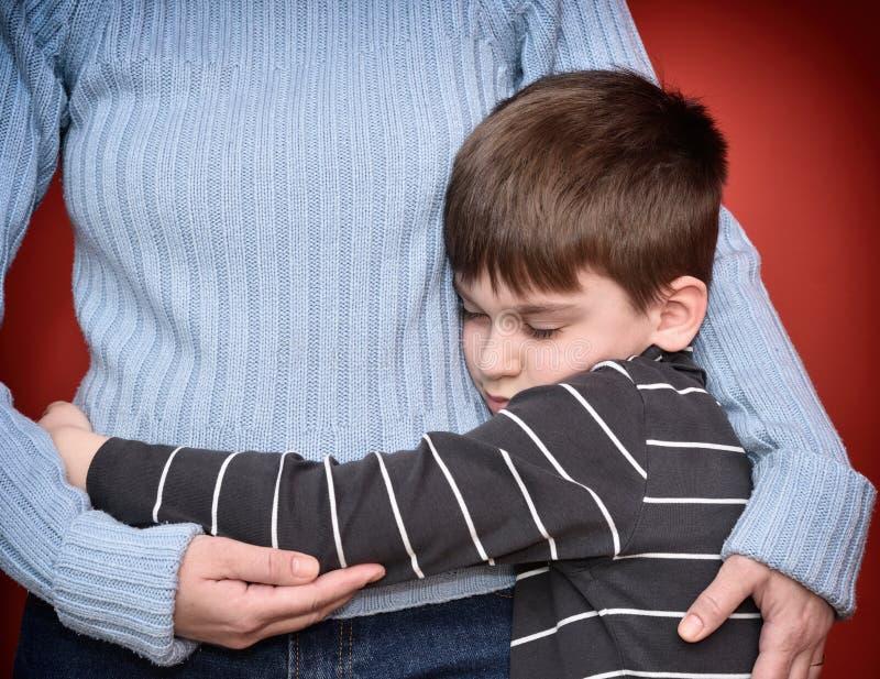 ragazzo i suoi giovani abbraccianti della madre fotografia stock