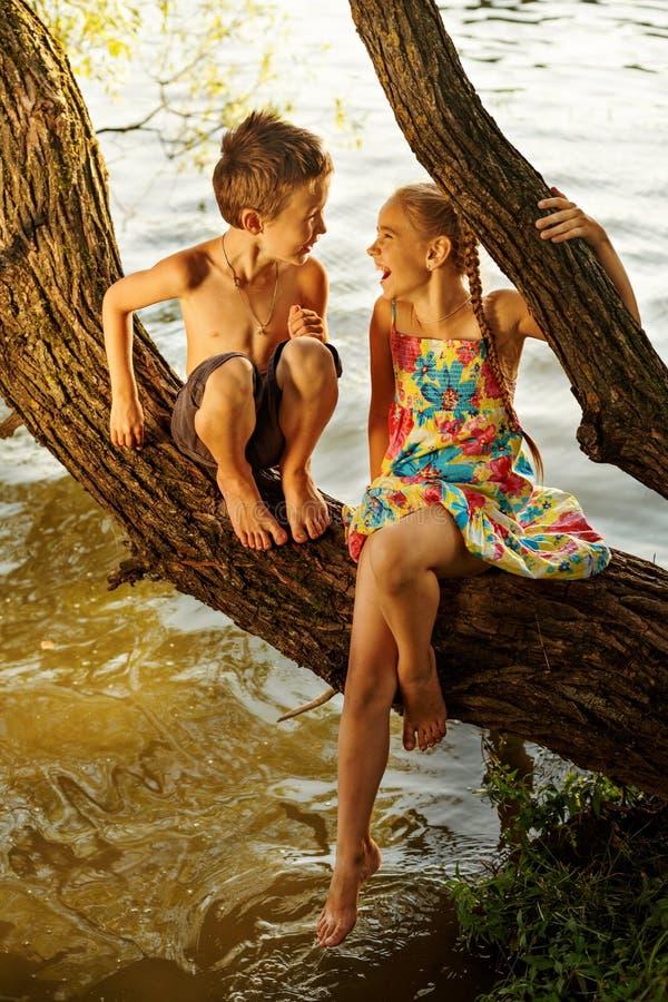 ragazzo impertinente e ragazza che si siedono su un ramo sopra acqua, ridendo fragorosamente, divertendosi conversazione fotografia stock