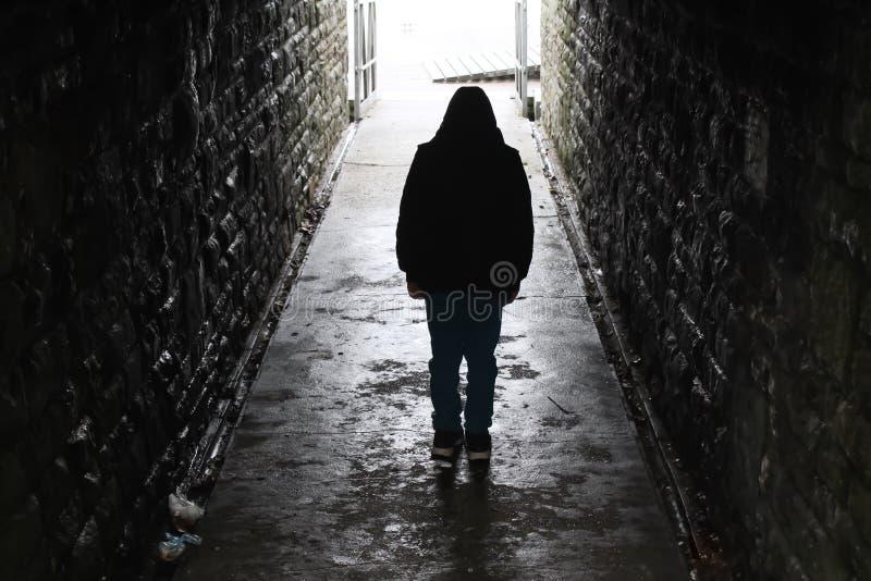 Ragazzo incappucciato in un tunnel sotterraneo fotografia stock libera da diritti