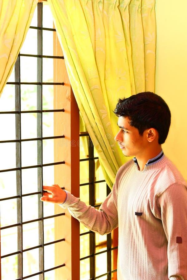 Ragazzo indiano solo che osserva fuori attraverso la finestra immagini stock
