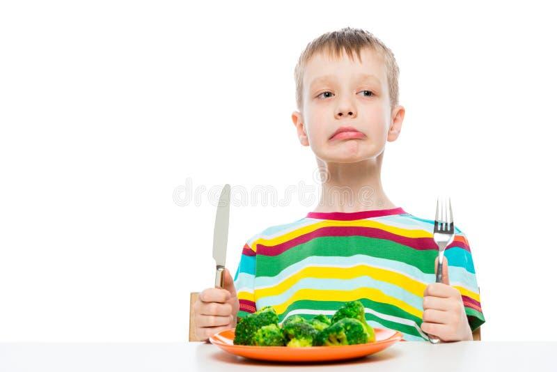 Ragazzo indignato con il cibo dei broccoli, ritratto isolato su bianco immagini stock
