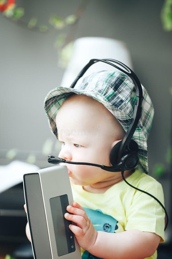 Ragazzo infantile del bambino del bambino sei mesi con l'altoparlante e le cuffie sani immagini stock